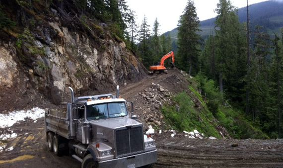 excavator and dump truck in mountains